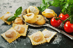 Homemade fresh Italian ravioli pasta. Homemade uncooked freshly prepared Italian ravioli pasta with fresh basil and tomatoes in a rustic kitchen in a close up Stock Image