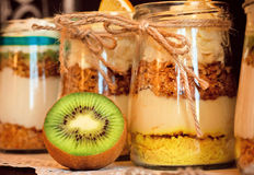 Homemade fresh milk dessert with kiwi and nuts in glass jars. Colorful pints for sweet tooth Stock Photo