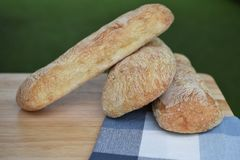 Food photography of fresh home made artisan ciabatta bread on a wood board with blue check pattern table cloth taken outside. Homemade fresh organic ciabatta Royalty Free Stock Photography