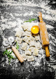 Homemade fresh ravioli with egg, a rolling pin and knife. Royalty Free Stock Photo