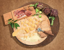 Homemade fresh ravioli with prosciutto,walnuts and artichoke,paced on a rustic round centerpiece. Stock Photo