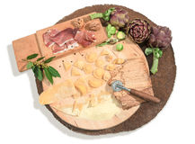 Homemade fresh ravioli with prosciutto,walnuts,brussels sprouts,artichoke and aromatic herbs paced on a rustic round centerpiece. Stock Photography