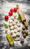 Homemade fresh ravioli with a rolling pin, tomato and olive oil. On the stone table with flour. Top view Royalty Free Stock Image