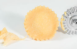Homemade fresh ravioli with wheel dough cutter, on white background. Close up of homemade fresh ravioli with wheel dough cutter, on white background Royalty Free Stock Photos