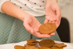 Homemade fresh round cookies in hands of a woman in green skirt and white sweater. Baking at home. Dessert for a family royalty free stock photos