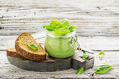 Homemade fresh spinach soup in a glass jar for a picnic in the fresh air on a wooden background with a slice of cereal. Useful bread. Selective focus Stock Images