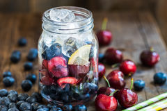 Homemade Fresh Summer Slushy. Ingredients for Summer Slushy from Blueberries, Cherries, Lemon and Ice in the Jar, on dark rustic background Stock Images