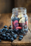 Homemade Fresh Summer Slushy. Ingredients for Summer Slushy from Blueberries, Cherries, Lemon and Ice in the Jar, on dark rustic background Stock Photography