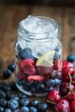 Homemade Fresh Summer Slushy. Ingredients for Summer Slushy from Blueberries, Cherries, Lemon and Ice in the Jar, on dark rustic background Royalty Free Stock Photos