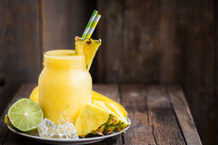 Homemade Fresh Summer Slushy. Summer Slushy from Mango, Pineapple, Lime and Ice with some ingredients nearby on dark rustic background Stock Photo