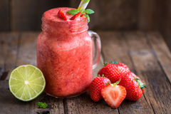 Homemade Fresh Summer Slushy. Summer Slushy from Strawberries, Lime and Ice with some ingredients nearby on dark rustic background Stock Photos
