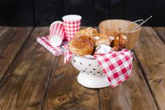 Homemade fried balls with powdered sugar. Napkin in red cage and glass. Brown wooden background. Traditional sweet Bake royalty free stock photography