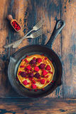 Homemade fried pancakes on a black cast iron skillet. Above are berries, raspberries, cranberries and blackberries. Royalty Free Stock Photography