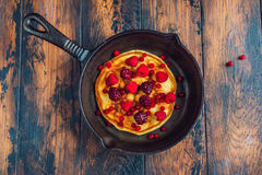 Homemade fried pancakes on a black cast iron skillet. Above are berries, raspberries, cranberries and blackberries. Royalty Free Stock Photos