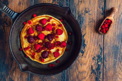 Homemade fried pancakes on a black cast iron skillet. Above are berries, raspberries, cranberries and blackberries. Wooden rustic brown background, top view stock photography