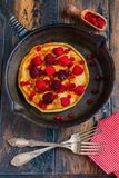 Homemade fried pancakes on a black cast iron skillet. Above are berries, raspberries, cranberries and blackberries. Royalty Free Stock Image