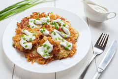 Homemade fried potato pancakes or latke traditiona. Hanukkah celebration food with greens and sour cream sauce served in dish on white rustic wooden table Royalty Free Stock Photos