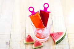 Homemade frozen popsicles made with watermelon on ice in glass on wooden background Stock Image