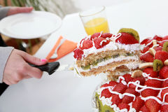 Homemade fruit cake is served with orange juice. Homemade fruit cake with strawberries and kiwi on the table is served with orange juice Royalty Free Stock Photography