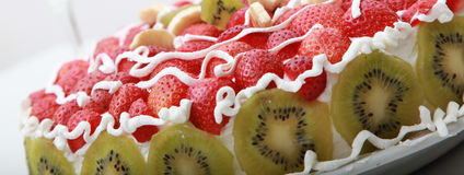 Homemade fruit cake with strawberries and kiwi. On the table is served Royalty Free Stock Photos