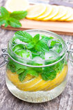 Homemade fruit drink with lemon mint and ice on the table Royalty Free Stock Image