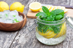 Homemade fruit drink with lemon mint and ice on the table Stock Photos