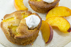 Homemade fruit muffins decorated with cream and fresh peach slic Royalty Free Stock Photography
