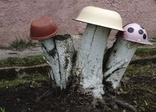 Homemade garden sculpture - mushroom amanita on the grass. The mushroom is made from an old plate and log. Upcycling. stock images