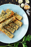 Homemade garlic bread on toast. Overhead view of plate of homemade garlic bread with cloves to side Royalty Free Stock Photos
