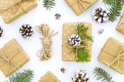 Homemade gift box decoration for Christmas. DIY hobby. Boxes are wrapped in kraft paper, tied with twine with twigs of. Thuja, cones and fir tree. Original gift stock photos