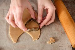 Homemade ginger biscuit cooking. Womans hands cut out dough in the shape of heart Stock Photo