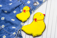 Homemade gingerbread chickens and jeans. On a white wooden background stock image