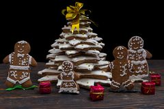 Homemade gingerbread Christmas tree with cute gingerbread family. With small gifts on wooden desk. Mockup for seasonal offers and holiday post card Royalty Free Stock Image