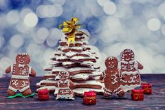 Homemade gingerbread Christmas tree with cute gingerbread family. With gifts on wooden desk on background of defocused silver lights. Mockup for seasonal offers Stock Photo