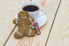 Homemade gingerbread cookie man and cup of coffee on wooden table Royalty Free Stock Images
