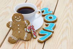 Homemade gingerbread cookie man with numerals 2017 and cup of coffee on wooden table Stock Photos