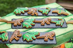 Homemade gingerbread cookies with the handmade icing decoration as funny dinosaurs. Wooden surface royalty free stock image