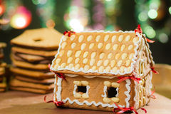 Homemade gingerbread cottage against a green Christmas tree Stock Photo