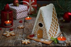 Homemade gingerbread house with pine branches, cones and biscuits on dark background. European Christmas traditions. Xmas holiday Stock Image