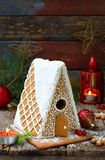 Homemade gingerbread house with pine branches, cones and biscuits on dark background. European Christmas traditions. Xmas holiday. Sweets Royalty Free Stock Photos