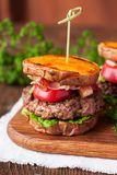Homemade gluten free burger with sweet potato, beef, guacamole royalty free stock images