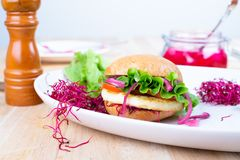 Homemade Gluten Free Halloumi Burger. Halloumi burger with lettuce, tomato, pickled red onion and beet sprouts. Gluten free bread stock photo