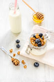 Homemade granola with blueberries in jar on white kitchen background Royalty Free Stock Image