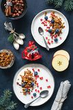Homemade granola, blueberries pomegranate seeds and yogurt. Healthy Christmas breakfast top view stock image