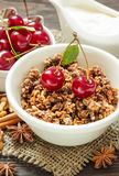Homemade granola and cream for breakfast. Homemade granola with cream, cinnamon and cherries for breakfast on a wooden background Royalty Free Stock Photography