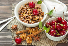 Homemade granola with cream and red cherries for breakfast on a. Homemade granola with cream, cinnamon and cherries for breakfast on a wooden background Royalty Free Stock Images