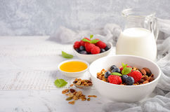 Homemade granola with fresh berries on white wooden background Stock Photos
