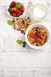 Homemade granola with fresh berries on white wooden background Royalty Free Stock Image
