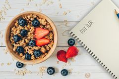 Homemade granola and fresh berries on wood table with note book and text diet plan concept, copy space.  royalty free stock images