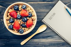 Homemade granola and fresh berries on wood table with note book and text diet plan concept, copy space.  royalty free stock photos